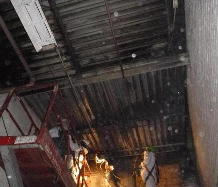 People Dressed in PPE on a Lift Cleaning a Fire Damaged Concrete Wall & Ceiling